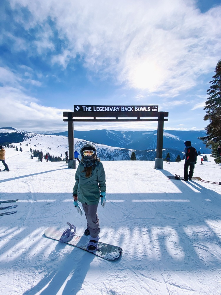 Snowboarder standing in front of Legendary Back Bowls in Vail, Colorado